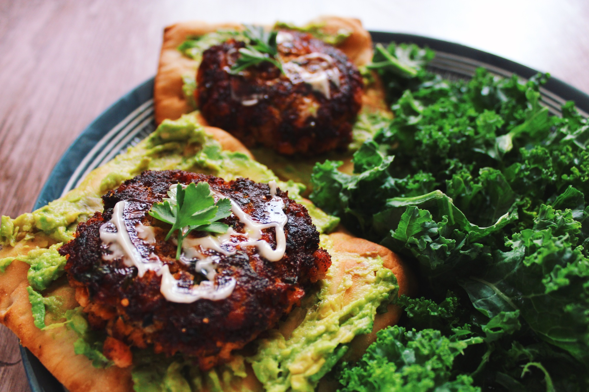 Salmon burgers on avocado flatbread toast with a kale salad
